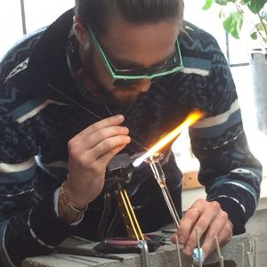 Man using torch in flame work of glass